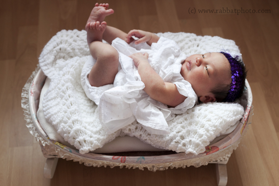 Newborn in doll bed