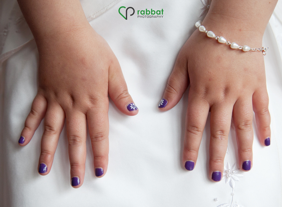 Child wearing nail polish with a flower design