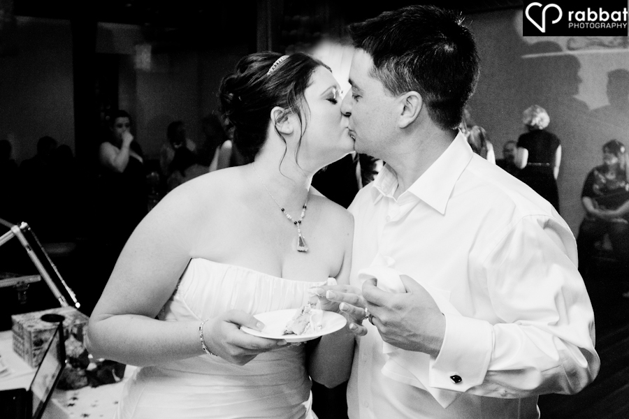 Kissing after cutting the cake Ancaster Old Mill winter wedding
