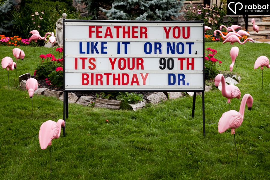 90th birthday sign surrounded by pink flamingos