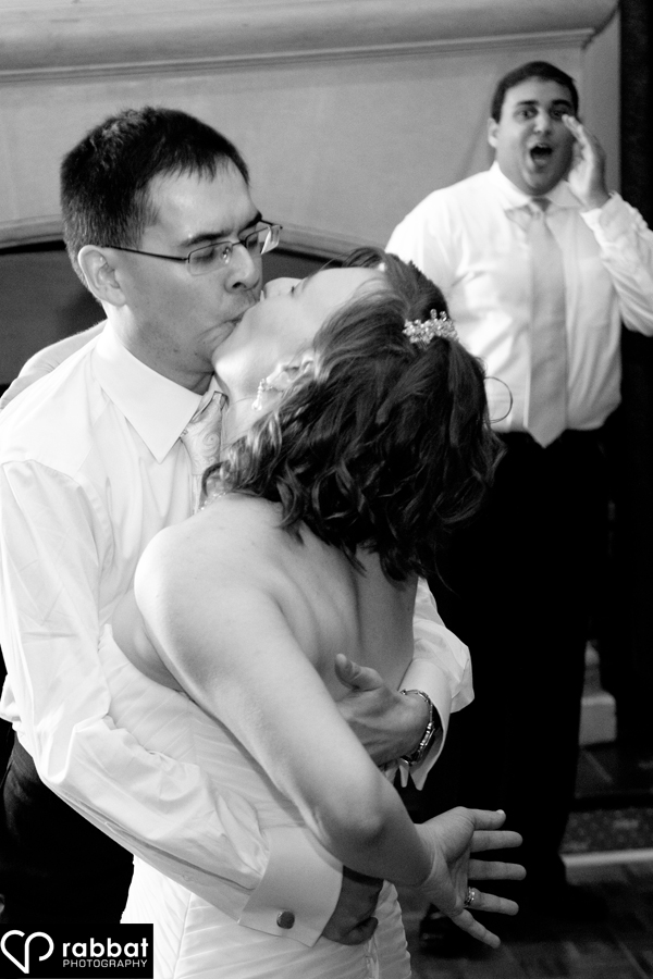 Bride and groom dancing, kissing and being cheered on