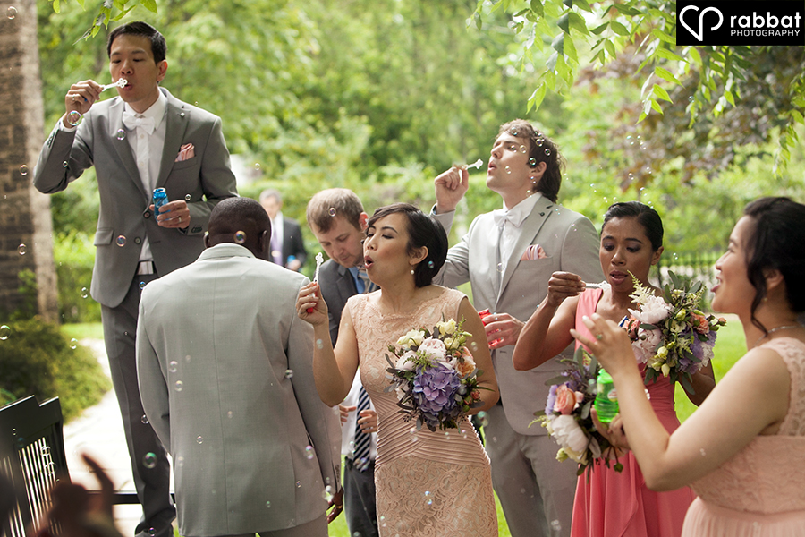 Wedding party blowing bubbles towards bride and groom