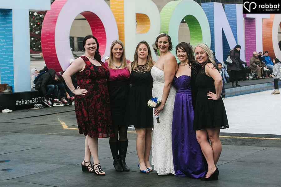 Bride with friends outside of Toronto sign