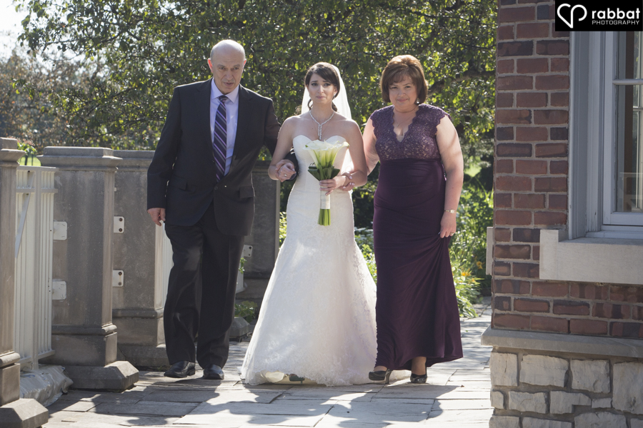 Bride walking down the aisle with both parents
