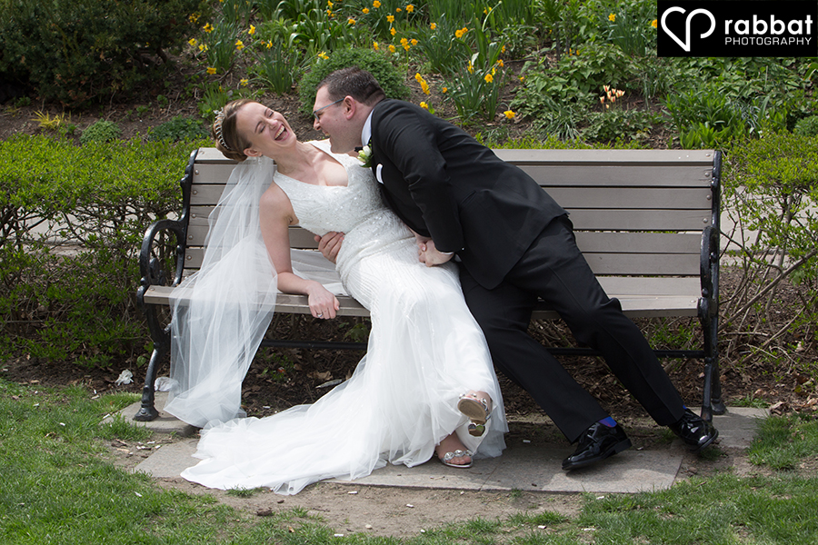 Wedding couple laughing on bench